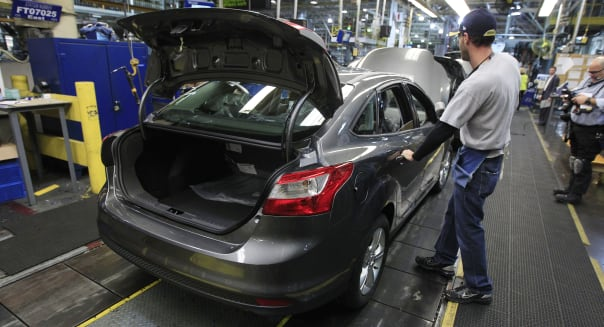 Ford Assembly (An assemblyman makes final adjustments to a Ford Focus on the assembly line at the Ford Michigan Assembly Plant i