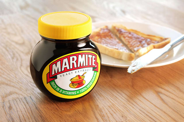 Leeds, United Kingdom - April 22nd, 2015: Jar of Marmite, unopened on wooden table top. Slice of toast on a white plate in backg
