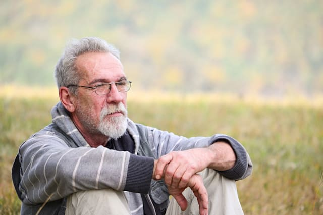 Portrait of an elderly, worried  man with a gray beard and glasses sitting on grass