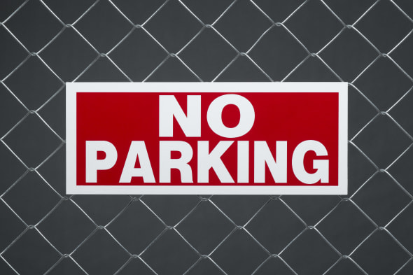 'No parking' sign on chain link fence