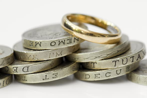 Gold wedding ring on top of pile of money