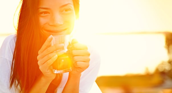 Asian woman drinking coffee in sun sitting outdoor in sunshine light enjoying her morning coffee. Smiling happy multiracial fema