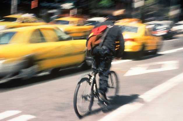USA New York Bike Messenger Making Delivery Through Traffic on a City Street