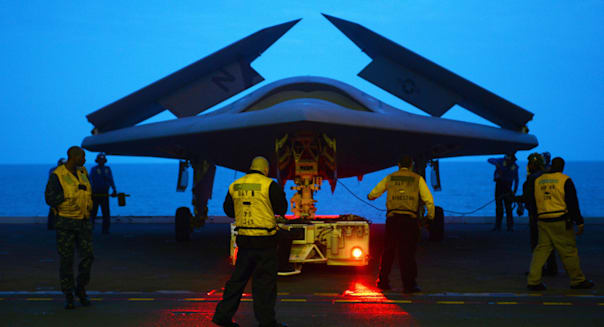 A US Navy X-47B Unmanned Combat Air System aircraft is towed into the hanger bay aboard the aircraft carrier USS George H.W. Bus