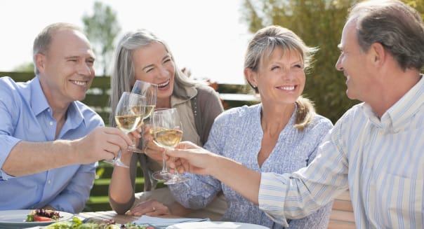 Senior couples toasting wine glasses at patio table
