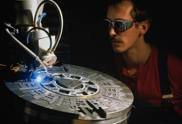 Worker watching clutch driving plate being welded by laser