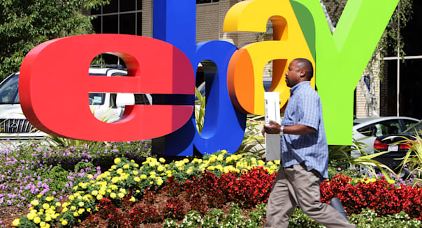 ebay headquarters in San Jose California. An employee carries a computer in front of the ebay logo