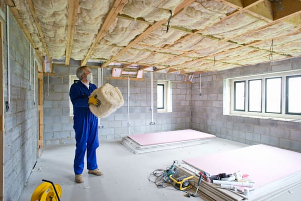 BECTMP Man holding ceiling insulation in house under construction