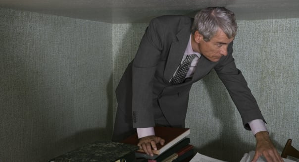 Mature businessman standing at desk stooping under low ceiling
