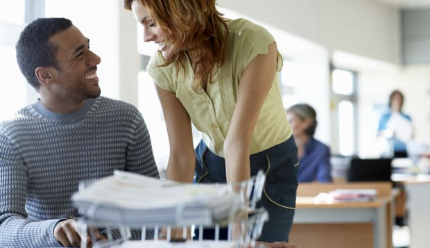 Businessman and woman smiling at each other in office