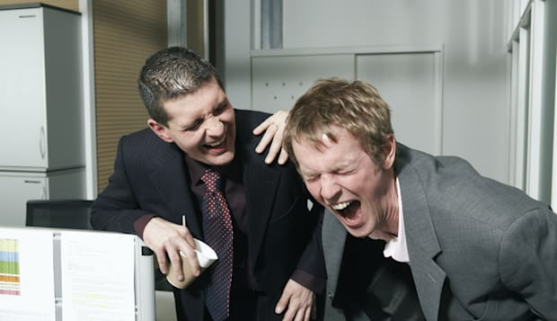 Two businessmen taking break in office, laughing