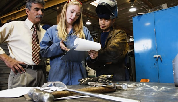 Manager and two manual workers looking at plans in factory