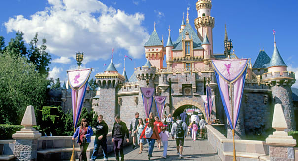 A view of the Disney castle and visitors at the entrance to Fantasyland in Disneyland