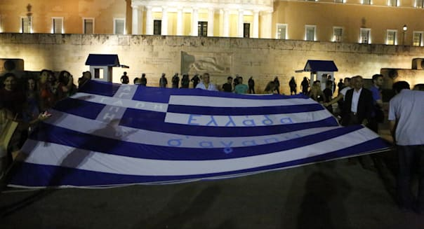 Protesters hold a large Greek flag at the anti-austerity