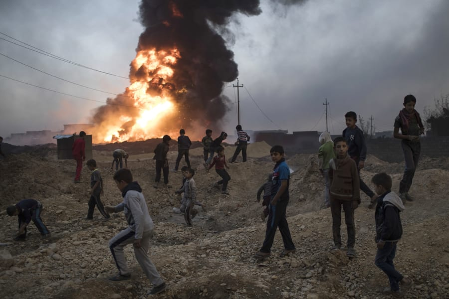 Children play next to a burning oil field in Qayara, south of Mosul on Nov 3. A senior military commander...