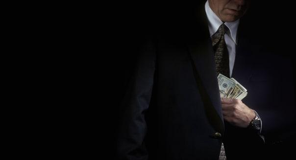 Businessman putting money in jacket