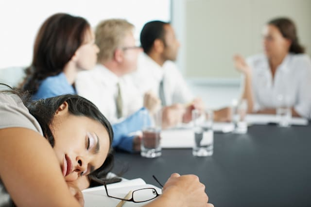 Businesswoman sleeping in conference room during meeting