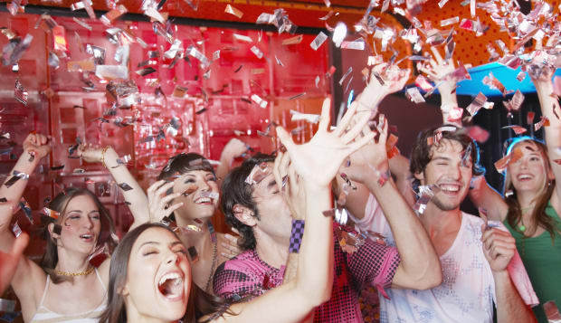 Group of people in a nightclub partying and throwing confetti