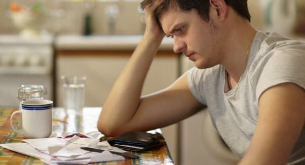 Young man holding head looking at receipts.