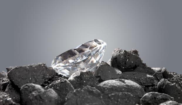 A diamond in a pile of coal shows the evolution of a precious gem.