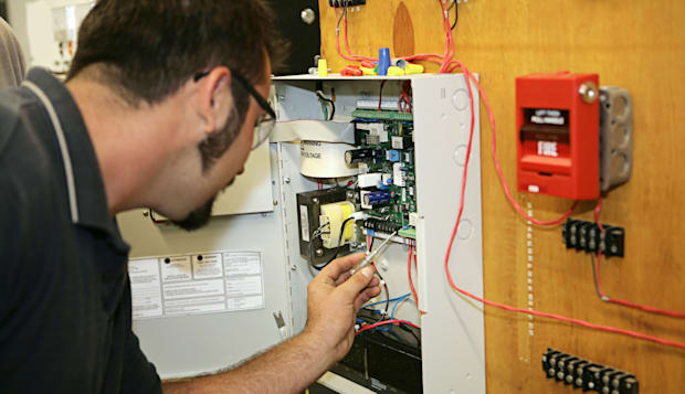 B7817M A student electrician wiring a fire alarm system at his technical college