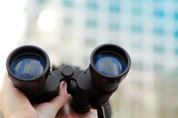 Businessman searching  office buildings with binoculars.