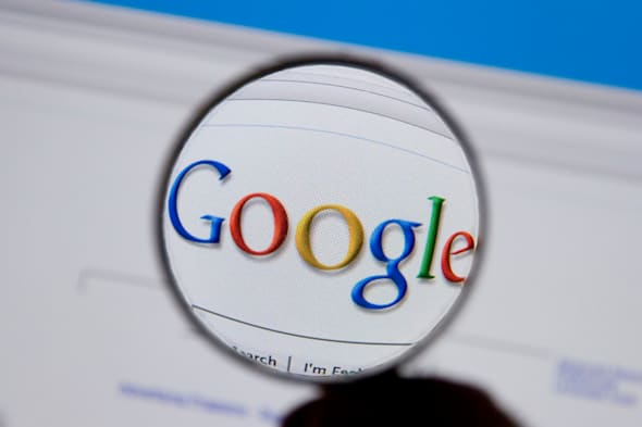 A magnifying glass highlights the Google search engine on a computer screen.
