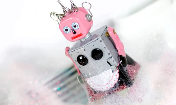 Female tin toy robot standing in front of dishes and covered in soap suds or washing up liquid bubbles