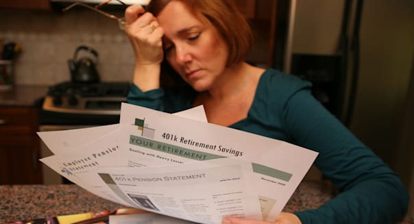 A woman is gripped by worry and anxiety as she looks over her investment statements.