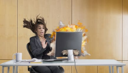 A woman recoiling as her computer explodes