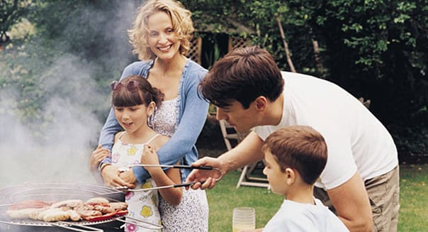 dv746073 (Royalty-free) Collection: Digital Vision Caption: Family Cooking A Barbecue in Their Garden Photographer: Digital Visi