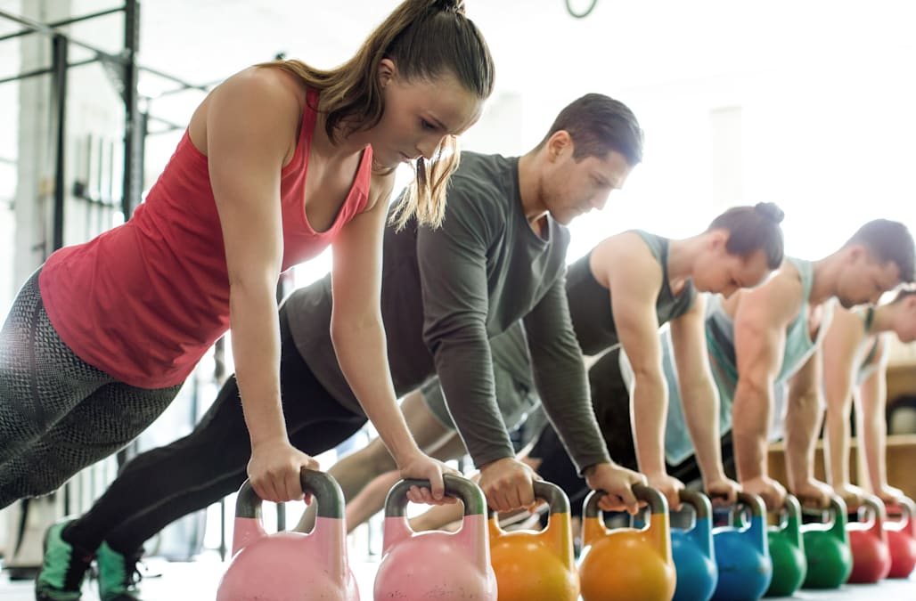 Gym class doing push-ups on kettlebells
