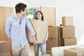 Couple carrying moving boxes into new home