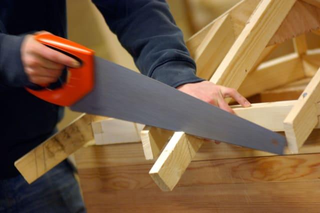 British carpenter sawing timber frame construction London UK