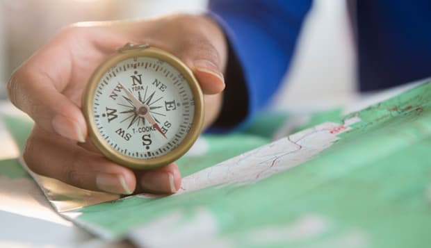 Mixed race woman holding map and compass