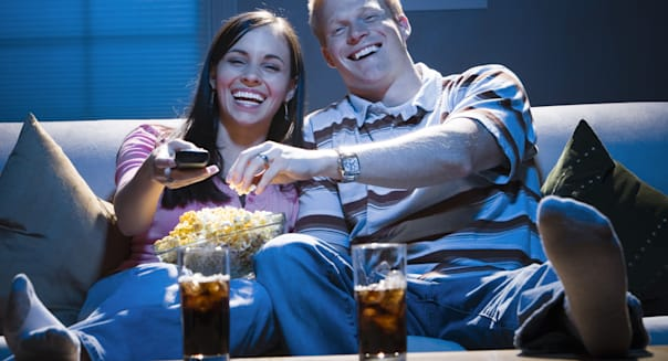 ADWDGT Couple sitting on sofa watching television with bowl of popcorn smiling  date; laughing; movie; tv; Adults; Beverages; Bo