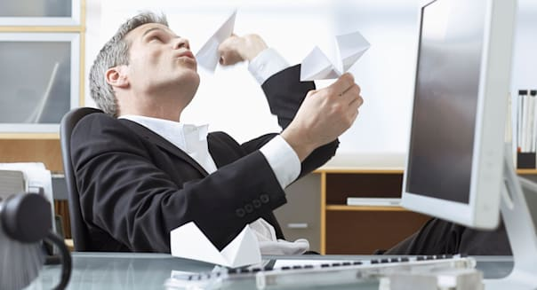 Businessman Playing with Paper Airplanes at Desk