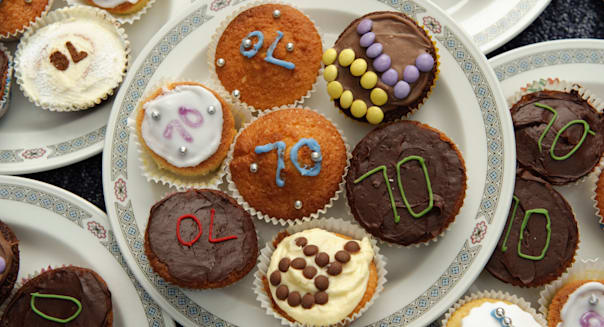 Plates of little iced cup cakes for a 70th birthday party UK