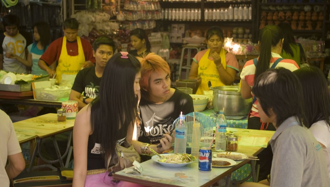 Group of young people sitting at a food stall and eating a snack, Suan Chatuchak Weekend Market, Bangkok, Thailand