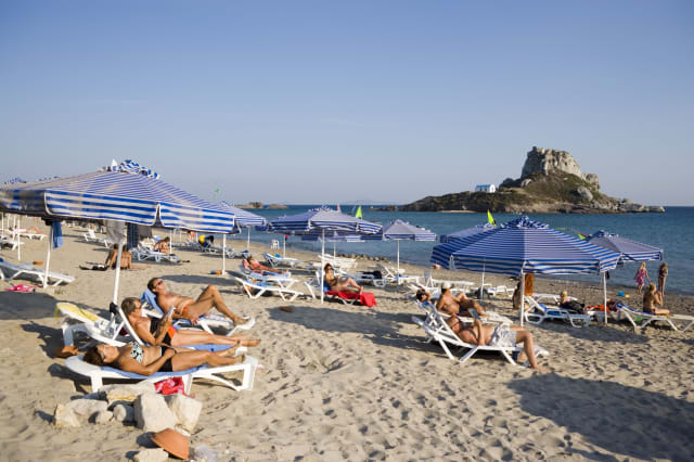 People sunbathing at Kefalos beach, Kastri island with chapel St. Nicholas in background, Kefalos, Kos, Greece