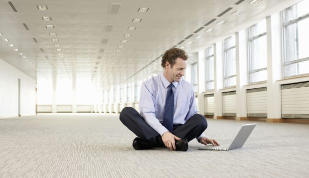 Businessman using laptop in empty office