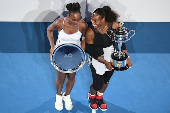 Serena Williams of the US holds the championship trophy after her victory in the women's singles final...