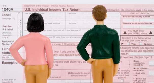 Figurines look at a US tax return.