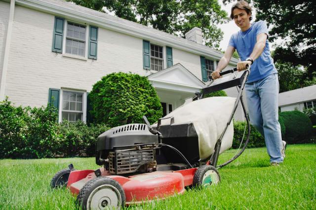 BAX1KK Man mowing front lawn  Man; mowing; lawn; caucasian; color; image; day; domestic; life; gardener; gardening; Hispanic; ho