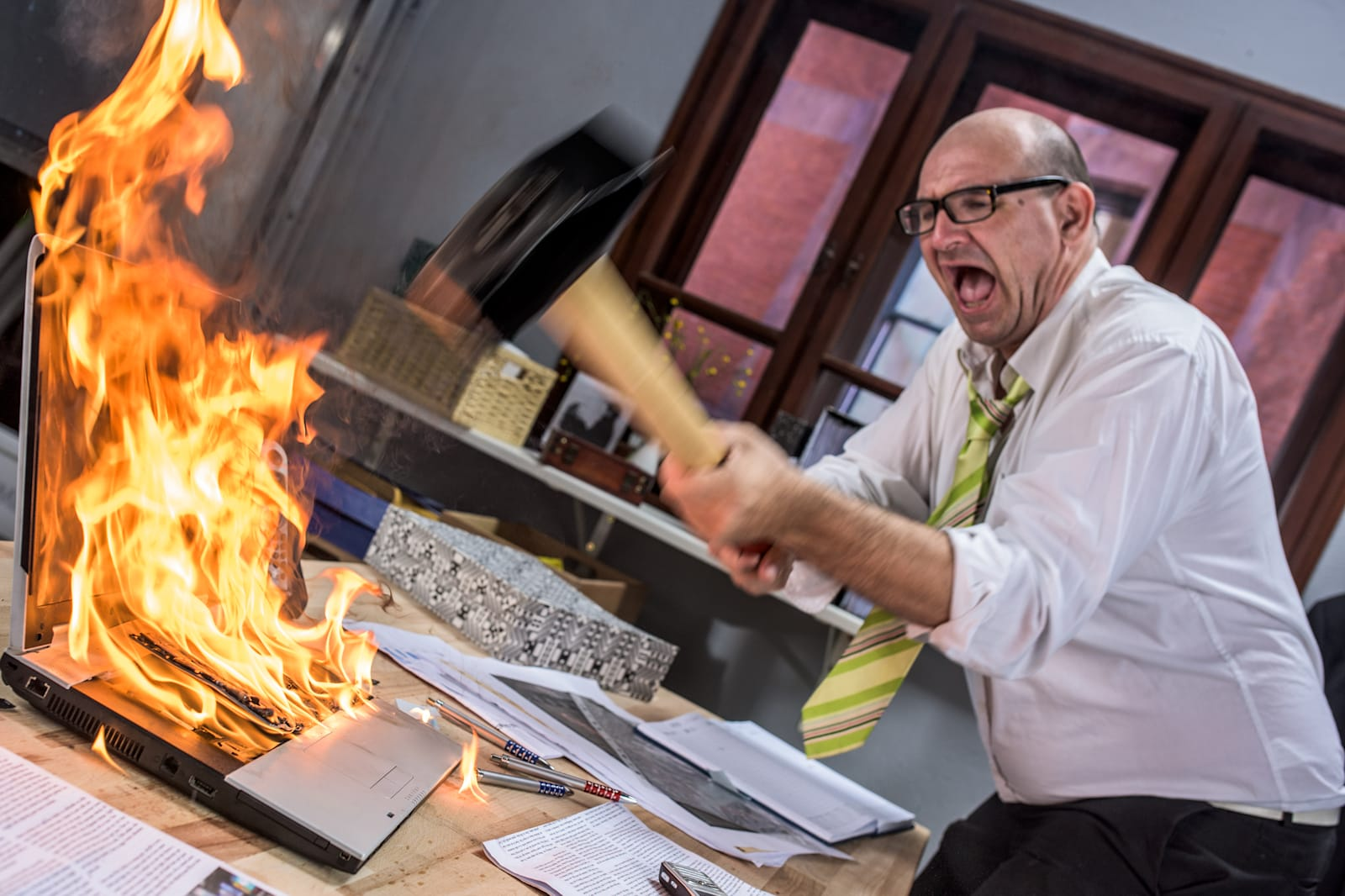 Mature adult businessman smashing laptop on fire with hammer