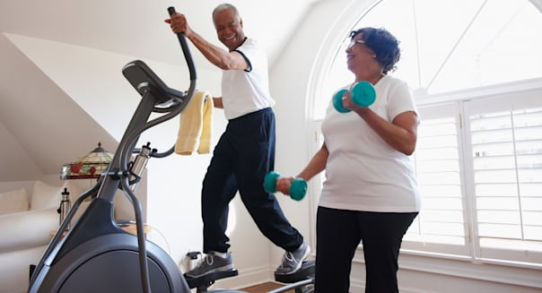 Smiling Black man using elliptical machine, wife using hand weights