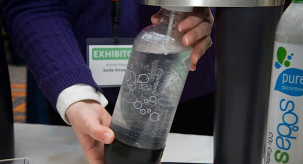 A representative from SodaStream demonstrates their home soda maker at the 2010 Green Products Expo in New York
