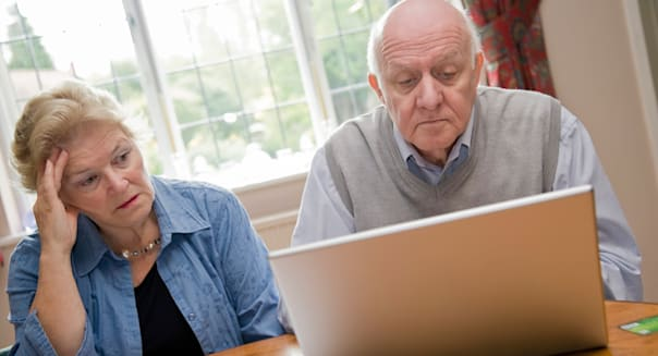 Mature older couple using a laptop computer, worrying about their bills and debts