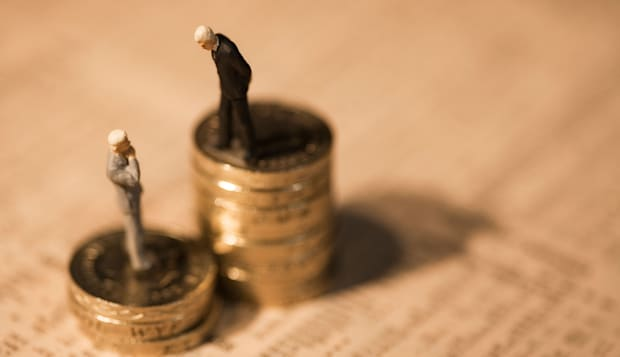 Miniature businessmen standing on coins on financial newspaper