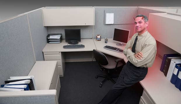 Businessman with horns in office cubicle